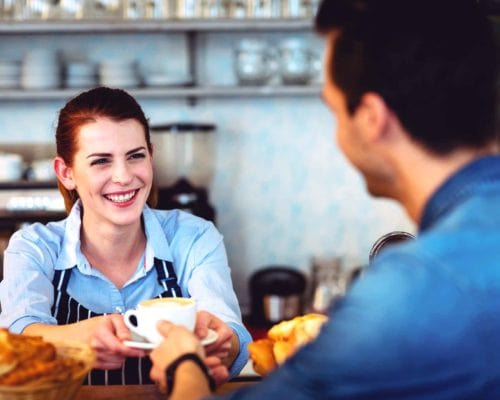 Woman serves coffee to customer in cafe